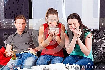 Freunde, die einen traurigen Film in Fernsehen aufpassen