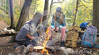 Freunde kochen traditionelle Pfannkuchen über einem offenen Feuer im Campingplatz bei einer Wanderung im Freien stock video