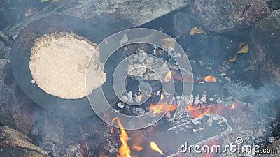 Freunde kochen traditionelle Pfannkuchen über einem offenen Feuer im Campingplatz bei einer Wanderung im Freien stock video footage