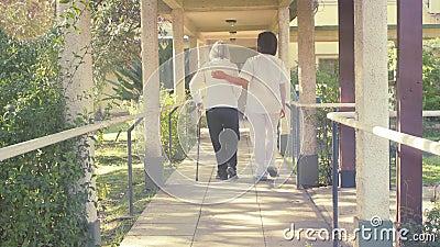 Freundliche Ärztin begrüßt Wiedergutmachung von älteren Patienten mit Gehhilfe im Freien stock video