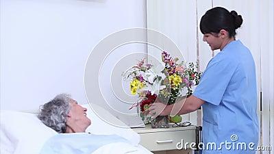 Fridfull hög kvinna som talar på en sjuksköterska som ger en bukett av blommor lager videofilmer