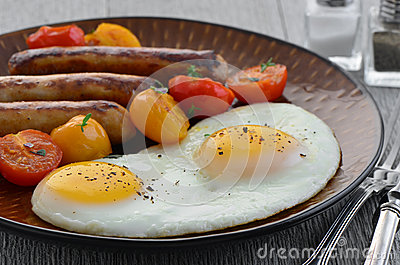 Fried eggs, sausage and cherry tomatoes