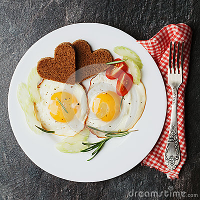 Free Fried Eggs With Fresh Vegetables And Toast In Shape Of Heart On White Plate Stock Photos - 63438283