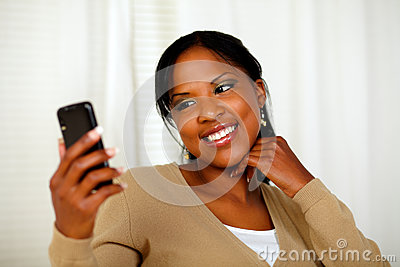 Friendly black woman sending a text message