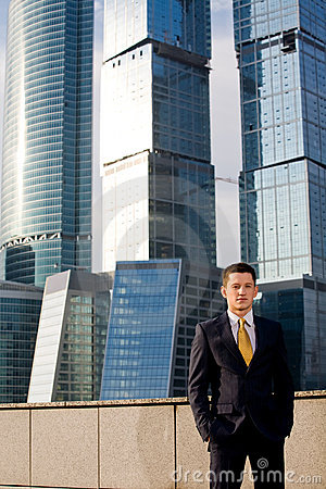 Friendly businessman standing against skyscraper