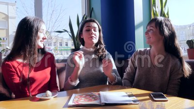 Friendly embrace, happy girlfriends Talking in restaurant sitting at table. Near window stock video footage