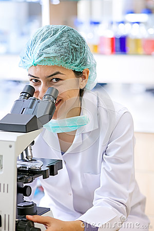 Friendly female lab technician using a microscope.