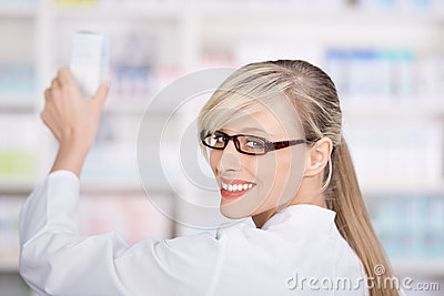 Friendly female pharmacist stores the medicines