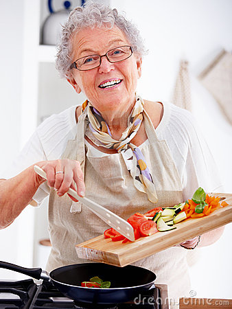 Friendly older woman happily cooking a meal