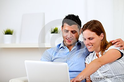 Friendly young couple using laptop together