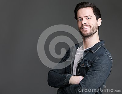 Friendly young man smiling with arms crossed