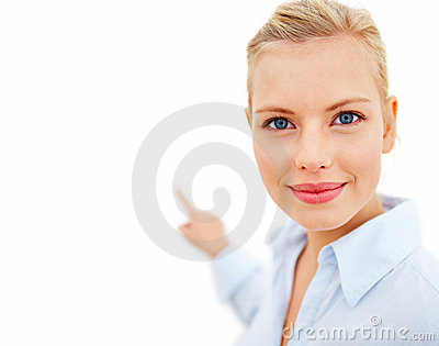 Friendly young woman pointing at space to copy