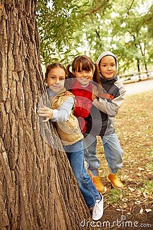 Friends behind tree