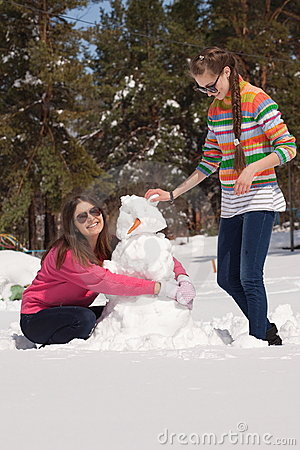Friends building snowman