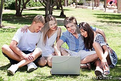 Friends enjoying movie in park on laptop
