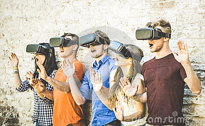 Friends group playing on vr glasses outdoors - Virtual reality Stock Photo