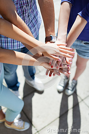 Friends with hands stacked in unison