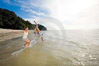 Friends having fun jumping into the sea