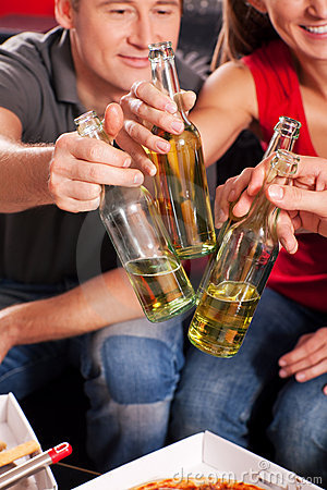 Friends having a party and clinking bottles