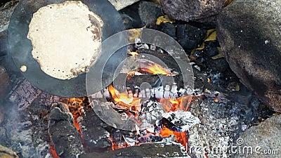 Friends lagar traditionella pannkakor över en öppen brand i lägret utomhus under en hike stock video