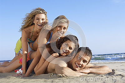 Friends Lying On Each Other At Beach