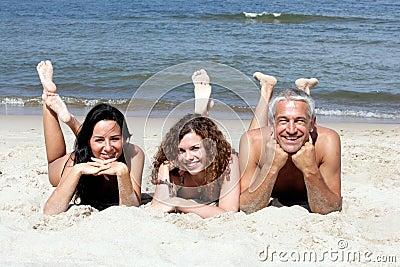 Friends lying on sandy beach
