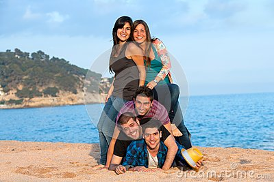 Friends making human pile on beach.