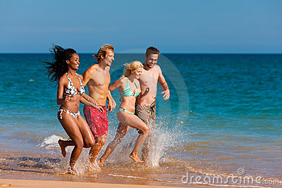 Friends running on beach vacation