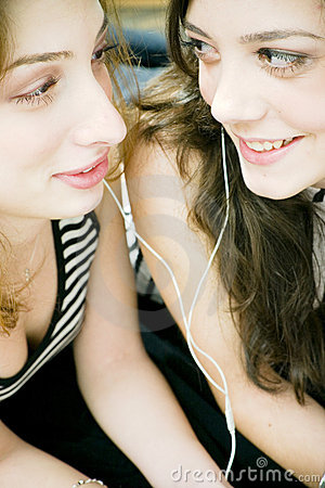 Friends sharing headphones