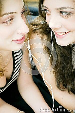 Friends sharing headphones