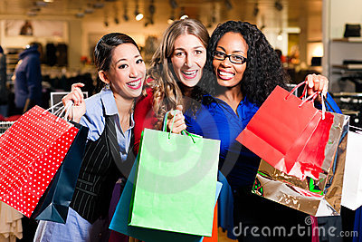 Friends shopping with presents in mall