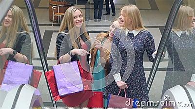 Friends shopping. Two beautiful young women taking. Escalator in shopping mall stock video footage
