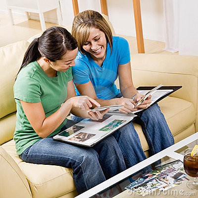 Free Friends Sitting On Sofa Looking At Photographs Royalty Free Stock Photo - 6603145