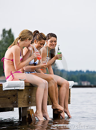 Friends sitting on pier drinking soda