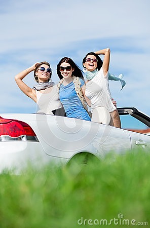 Friends stand in the auto with hands up