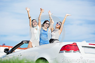 Friends stand in the automobile with hands up