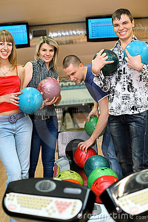 Friends stand near tenpin bowling with balls