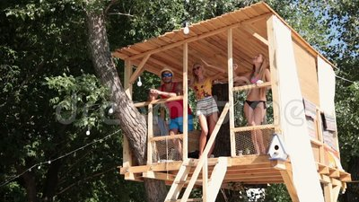 Friends on vacation looking at sea from tree house stock video