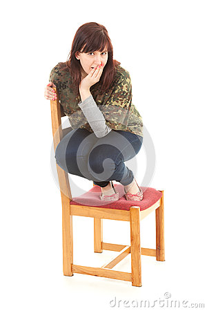 Frightened fat teenage girl on chair, full length