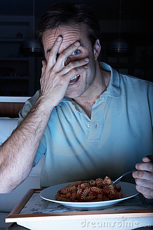 Frightened Man Enjoying Meal Watching TV