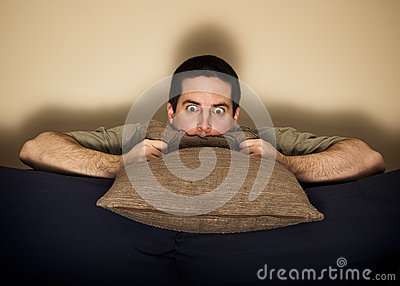 Frightened man hides behind a pillow