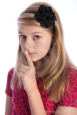 Frightened school girl child makes keep quiet sign