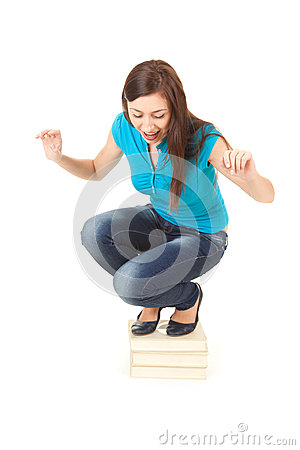 Frightened young woman squat on the pile of books