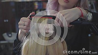 Friseur lässt eine Kräuselung auf dem Haar an den Wurzeln Volumenfrisur addieren stock footage