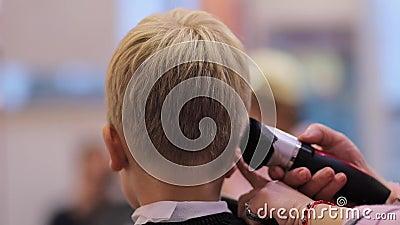 Friseur schneidet Haare mit Kappenholz auf den Kopf des Jungen stock video footage