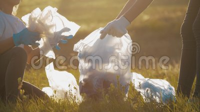 Frivilligmansfamiljen plockar upp sopor och plaster städar parken med en sopsäck Teamarbete och ekologi lager videofilmer