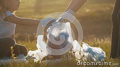 Frivilligmansfamiljen plockar upp sopor och plaster städar parken med en sopsäck Teamarbete och ekologi stock video