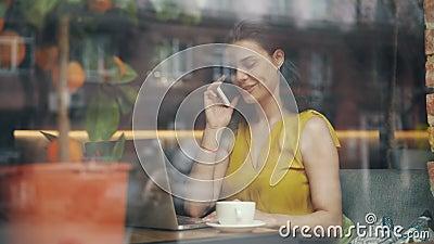 Frohe Geschäftsfrau, die am Handy spricht und Laptop in der Cafeteria verwendet stock video footage