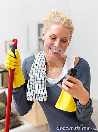 Frohe junge Frau, die Ihr Haus säubert