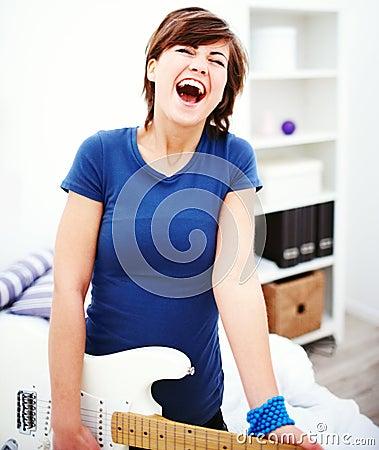 Frohe junge Frau, die zu Hause eine Gitarre spielt